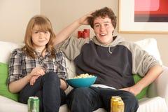 hålla ögonen på för tv för sofa för par sittande tonårs- Arkivfoto