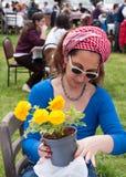 Hållande blomma för kvinna Arkivfoto