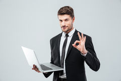 Hållande bärbar dator för attraktiv ung affärsman och ok tecken för visning Arkivfoto