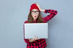 Hållande bärbar datordator för kvinna och se kameran Royaltyfria Bilder