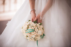 Hållande bröllopbukett för brud från vita rosor Arkivfoton
