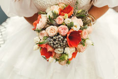 Hållande bröllopbukett för brud med röda och vita blommor Arkivfoton