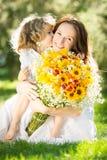 Hållande bukett för kvinna och för barn av blommor Arkivbilder