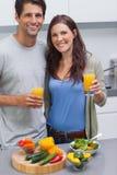 Hållande exponeringsglas för förtjusta par av orange fruktsaft Royaltyfri Bild