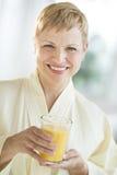 Hållande exponeringsglas för lycklig kvinna av fruktsaft Royaltyfri Foto