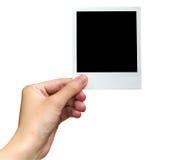 Hållande fotoram för hand på isolerad vit med den snabba banan Arkivfoto