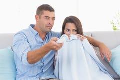 Hållande ögonen på fasafilm för par på soffan Royaltyfri Foto