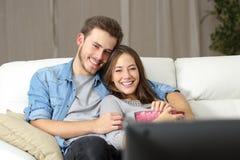 Hållande ögonen på film för lyckliga par på tv Royaltyfri Foto