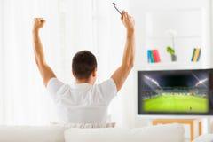 Hållande ögonen på fotboll för lycklig man på tv hemma Arkivbilder