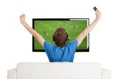 Hållande ögonen på fotboll på TV:N Royaltyfria Bilder