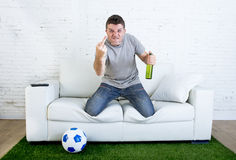 Hållande ögonen på lek för ilsken fan för fotboll fanatisk på den hemmastadda soffan för television som gör en gest rubbning Royaltyfri Foto