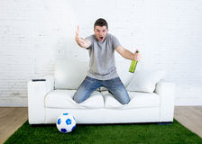 Hållande ögonen på lek för ilsken fan för fotboll fanatisk på hållande öl för television som gör en gest upprivet och galet ilske Royaltyfri Bild