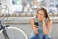 Hållande ögonen på massmedia för lycklig flicka i en smart telefon Arkivbild