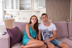 Hållande ögonen på television för barnpar tillsammans hemma Royaltyfria Foton