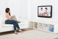 Hållande ögonen på television för kvinna, medan sitta på soffan Arkivfoto
