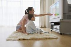 Hållande ögonen på television för moder och för son Fotografering för Bildbyråer