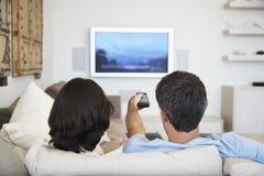Hållande ögonen på television för par i vardagsrum Fotografering för Bildbyråer