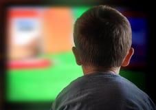 Hållande ögonen på television för pojkebarn hemma Arkivfoto