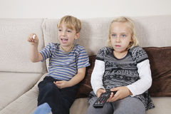 Hållande ögonen på television för syskongrupp Royaltyfria Foton