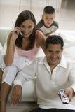Hållande ögonen på TV för familj medan moder på mobiltelefonen Royaltyfri Bild