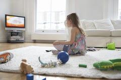 Hållande ögonen på TV för flicka med leksaker på golv Royaltyfri Bild