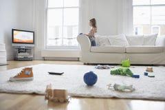 Hållande ögonen på TV för flicka med leksaker på golv Royaltyfria Foton