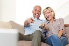Hållande ögonen på tv för gladlynta par hemma Royaltyfri Bild