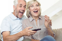 Hållande ögonen på tv för gladlynta par på soffan Royaltyfria Foton