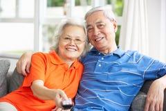 Hållande ögonen på TV för höga kinesiska par på sofaen hemma Royaltyfri Foto