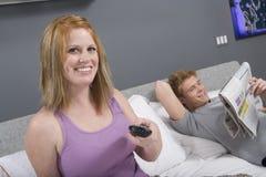 Hållande ögonen på TV för kvinna i sovrum Royaltyfri Bild