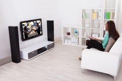 Hållande ögonen på TV för kvinna i vardagsrum Royaltyfri Foto