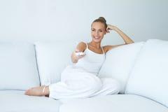 Hållande ögonen på tv för lycklig kvinna på soffan Arkivbild