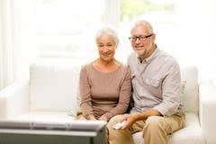 Hållande ögonen på tv för lyckliga höga par hemma Royaltyfria Bilder