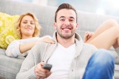 Hållande ögonen på TV för lyckliga par hemma Arkivbilder