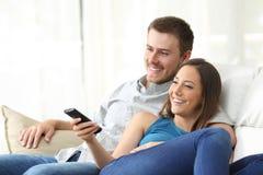 Hållande ögonen på TV för lyckliga par hemma Royaltyfri Bild