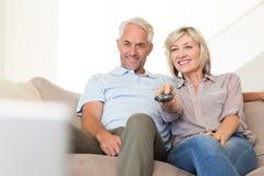 Hållande ögonen på tv för lyckliga par på soffan Royaltyfria Bilder