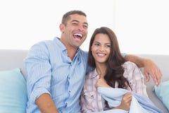 Hållande ögonen på tv för lyckliga par på soffan Arkivfoton