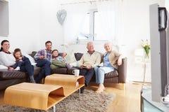 Hållande ögonen på TV för mång- utvecklingsfamilj tillsammans Arkivbilder