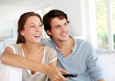 Hållande ögonen på tv för par Fotografering för Bildbyråer