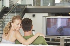 Hållande ögonen på TV för par hemma Royaltyfria Bilder