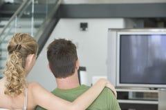 Hållande ögonen på TV för par hemma Royaltyfri Bild