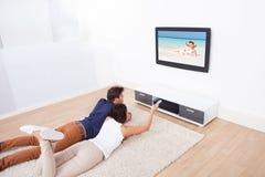 Hållande ögonen på tv för par hemma Arkivbilder