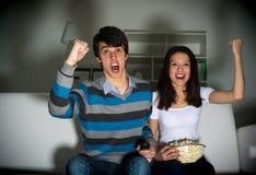 Hållande ögonen på TV för par på soffan Arkivbild