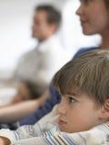 Hållande ögonen på TV för pojke och för familj hemma Royaltyfria Foton