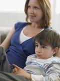 Hållande ögonen på TV för pojke och för moder hemma Royaltyfri Bild