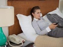 Hållande ögonen på tv för trött affärskvinna i hotellrum Arkivfoto