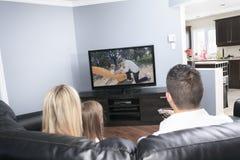 Hållande ögonen på TV för ung familj tillsammans hemma Royaltyfri Fotografi