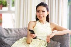 Hållande ögonen på TV för ung kinesisk kvinna på sofaen hemma Royaltyfri Fotografi