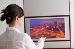 Hållande ögonen på tv för ung kvinna hemma Arkivbild