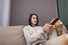 Hållande ögonen på TV för ung kvinna i vardagsrum Royaltyfri Fotografi
